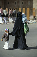 Asia, arabic Peninsula, Yemen, Sana'a, arabic women with a kid walking along the street, dressed with a traditional Galabiya, Khimar