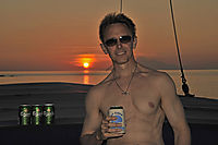 Asia, Indonesia, Komodo Island, cosy evening with friends on board of the Philippine Siren, drinking a beer in the sunset