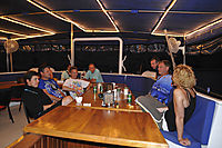 Asia, Indonesia, Komodo Island, cosy evening with friends on board of the Philippine Siren, eating and drinking, eat and drink