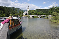 Europe, Slovenia, Lake Bohinjsko Jezero, bridge and church of Ribec Laz, lake Bohinj, child is looking from the jetty to a boat