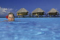 Oceania, French Polynesia, Tuamotus, South Sea Islands, South Pacific, Manihi, girl is relaxing in the pool in front of overwater bungalows, holiday feeling