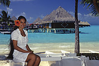 Oceania, French Polynesia, Society Islands, South Sea Islands, South Pacific, Bora Bora, Island beauty on an outrigger boat in front of overwater bungalows in a lagoon