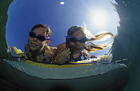 Europe, Austria, Tyrol, Lake Plansee, against the sunlight, kids looking under water with swimming goggles, freshwater