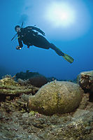 Asia, Turkey, Dalaman, Fethiye, Lykia World Ölüdeniz, diver with a torch above an amphora, against the sunlight, relics, antiquities receptacle, container under water