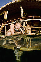 Asia, Indonesia, West Papua, Raja Ampat, Papua Paradise Resort, man with dog at the jetty, split image