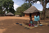 Africa; Mozambique; Tofo Beach, Inhanbane, women with child is sitting at the ground, hootch